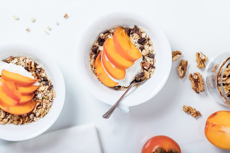 Yogurt with fruit and nuts on white background