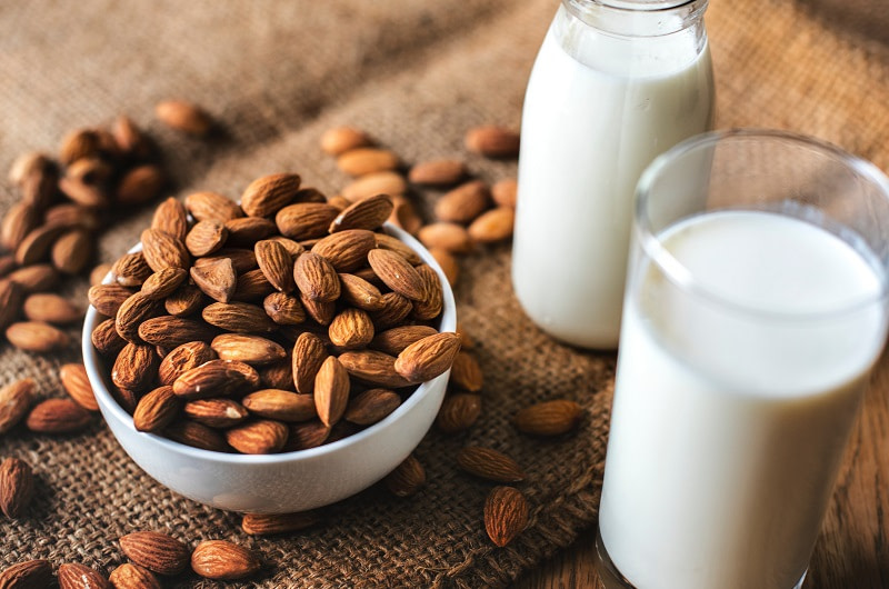 Almonds in a dish and milk in a cup