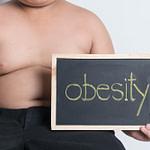 A fat boy holding a blackboard saying obesity