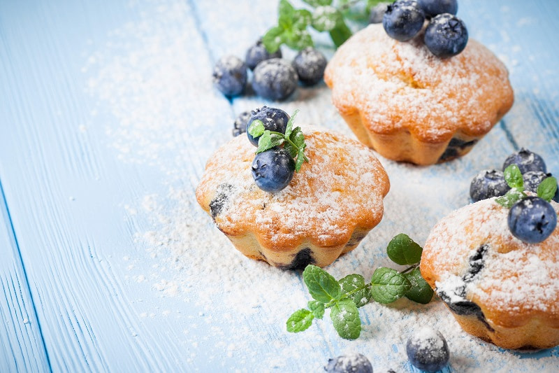 Homemade muffins with blueberries on blue background