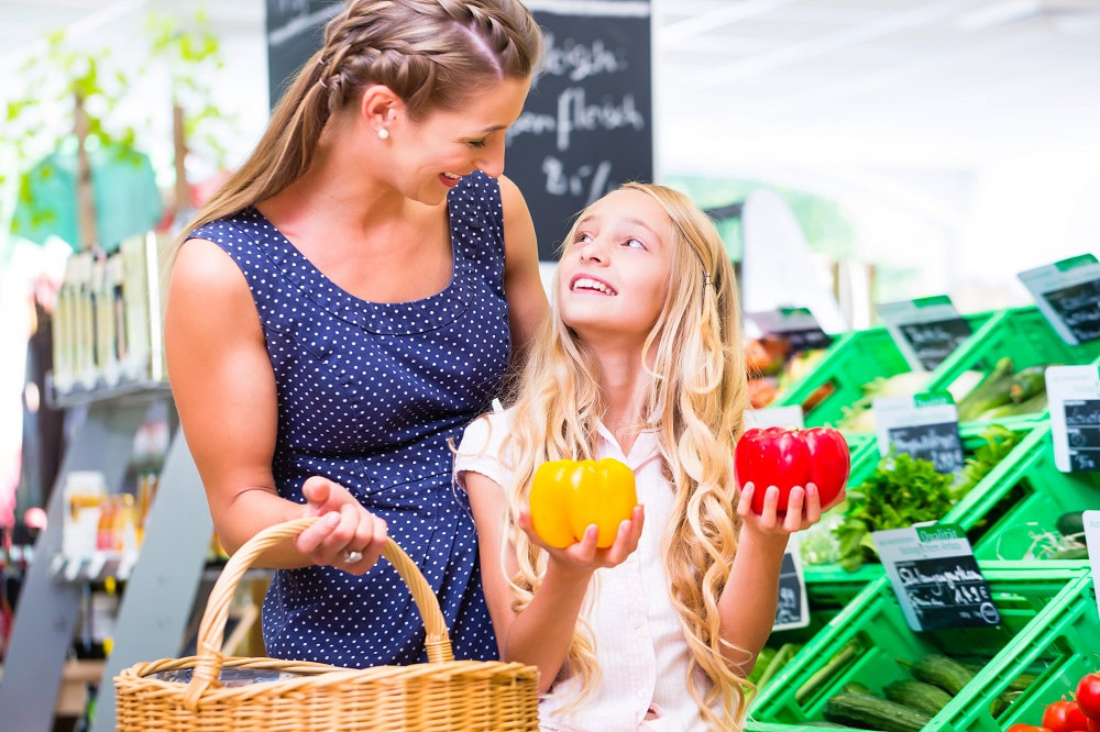 Mother and daughter buying healthy food in the supermarket